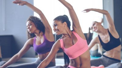 Three women stretch in an exercise class, part of their ADHD stress management plan.