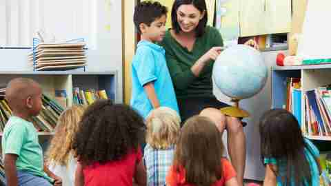 A teacher giving an attention grabbing presentation, a good strategy to improve classroom behavior.
