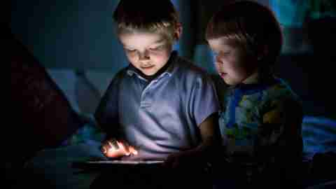 A boy with minecraft addiction plays at night as his brother watches.