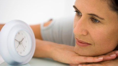 A woman looks at her alarm clock and thinks about how to be on time