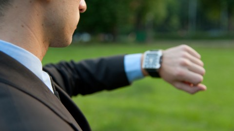 A man checks his watch, to remind himself of how to be on time