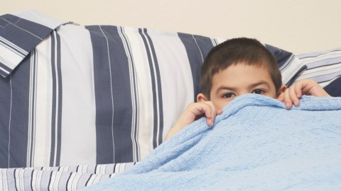 A boy with ADHD sticking his head out from under the covers because he can't fall asleep.