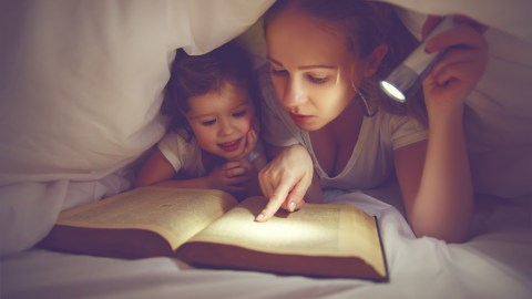 A girl with ADHD reading under the covers because she can't sleep.