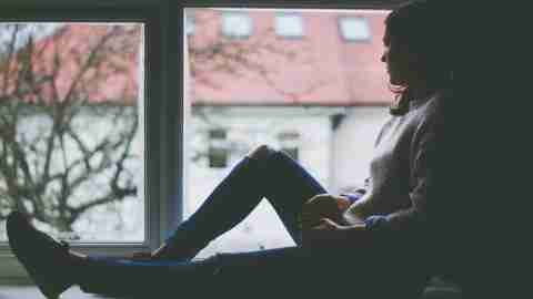 A woman with ADHD stares out a window, depressed that her loved ones don't understand ADD..