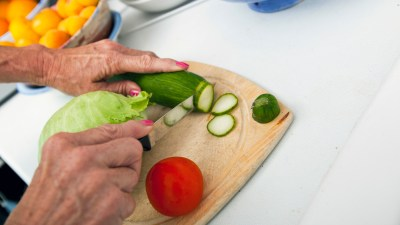 A woman cutting healthy vegetables, a key part of a good adhd diet for kids.