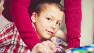 Boy with ADHD looking at camera while completing writing assignment
