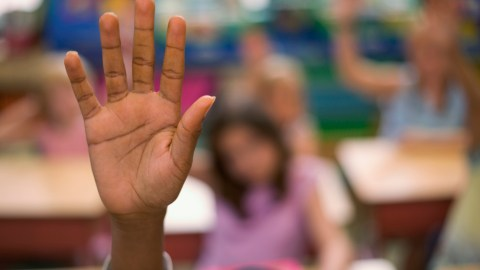 A hand raised to discuss parents and teachers working together