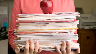 A stack of papers with an apple on top, representing parents and teachers working together