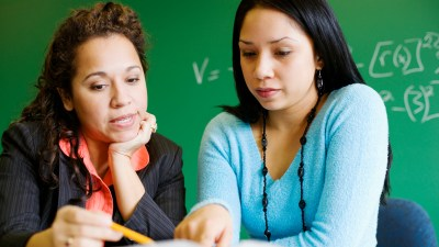 A teacher and parent duo review an IEP together, a key thing to do before school starts.