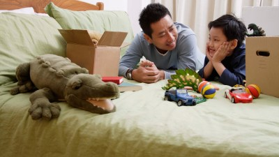 A dad helps his son with ADHD put toys in a box to clean up his messy bedroom.