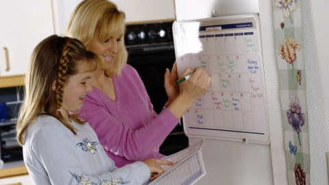 An ADHD mom and her child use a calendar to stay organized.