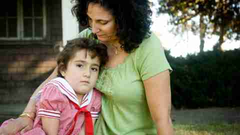 A mother sits with her daughter who has ADHD and Tourette's syndrome.