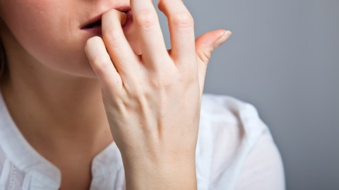 A woman with body-focused repetitive behaviors bites her nails due to anxiety, ADHD or depression