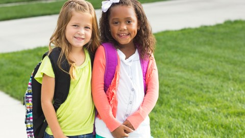 Two girls leave school with their backpacks, ready to use ADHD homework strategies to finish assignments.
