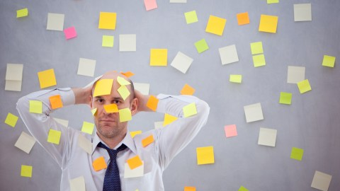 A man with ADHD covered in reminder notes