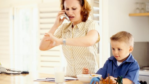 A mom looks at her watch and is stressed out because her son with ADHD is behind on his daily routine.