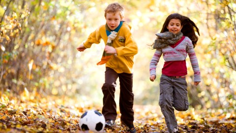 Two children with ADHD play soccer outside as part of their daily routine.