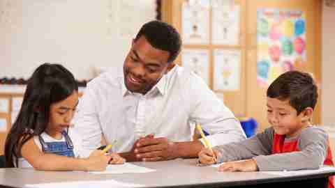 """A teacher works with two students at their desks after hearing parents say, """"My child hates school."""""""