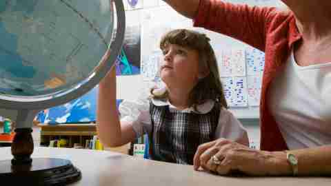 A student with ADHD looks at a globe with her teacher.