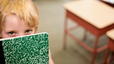 Boy with ADHD holds a notebook and reflects