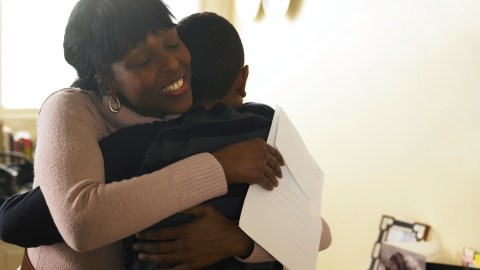 A mom hugs her child after obtaining paperwork for a 504 plan to meet her specific child's needs.