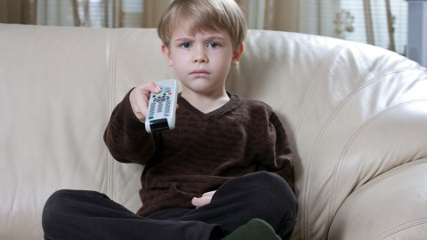 A boy holds a TV remote and watches a program about anger management for kids.