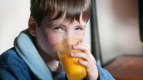 Blond boy drinks orange juice and looks at camera after taking ADHD medication