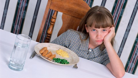 A girl looking upset next to her meal because her ADHD medication has decreased her appetite