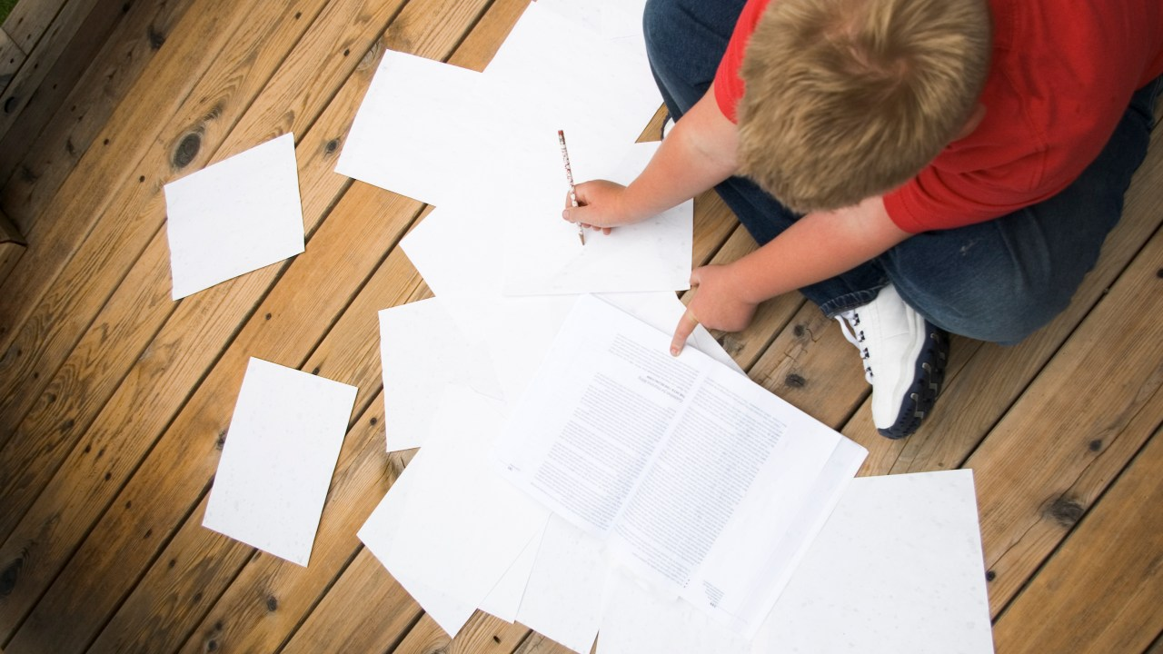 Boy working on his homework while sitting on the floor, using executive functions