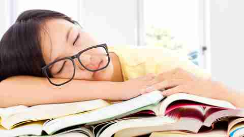 Tired girl with ADHD sleeping while studying