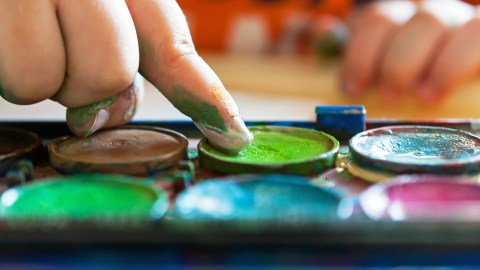 A child with sensory processing disorder finger paints to help manage symptoms