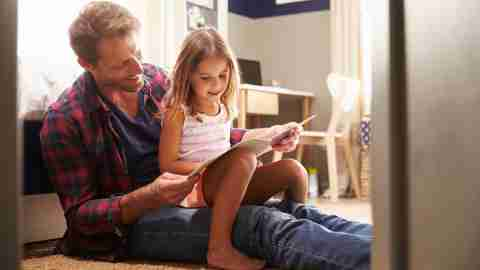 A father reads a book with his daughter about how to control emotions and avoid ADHD tantrums.