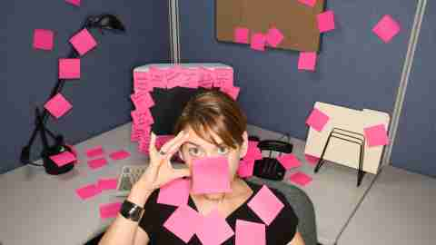 A woman with ADHD has post-It reminders all over her desk and face