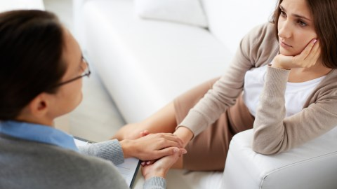 A therapist comforts her patient with ADHD on a couch