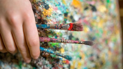 A person with ADHD holds three paintbrushes in front of a paint-spattered smock