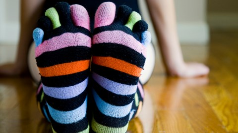 A child gets distracted staring at her colorful socks.