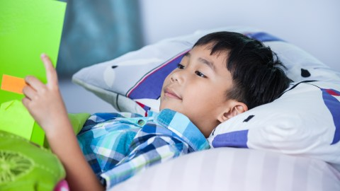 A boy reading in bed, a way children with ADHD can more effectively study