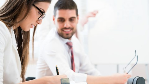 A woman writes notes on how to succeed with ADHD at work while a male coworker looks on.