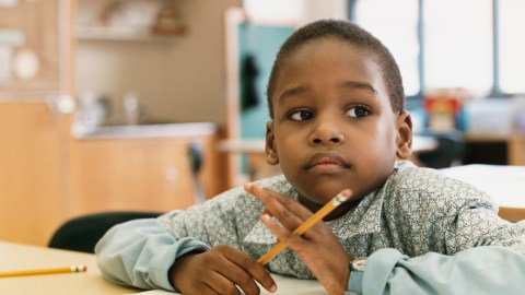 An apprehensive student contemplating his writing assignment, which 504 accomodations for adhd can help manage.