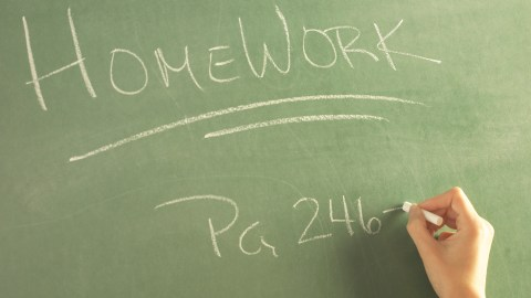 A teacher assigning homework on the blackboard, which 504 accomodations for adhd can help your child to complete by improving communication.