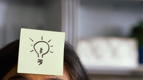 A woman with ADHD has a post-it with a lightbulb stuck to her forehead.