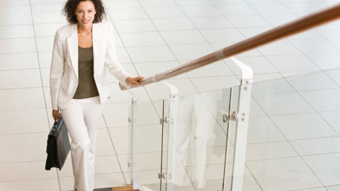 "A businesswoman stands at the bottom of a flight of stairs wondering, ""Should I tell my boss I have ADD?"""