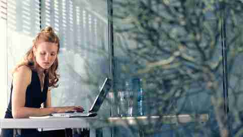 """A woman uses a laptop at a conference table and wonders, """"Should I tell my boss I have ADD?"""""""