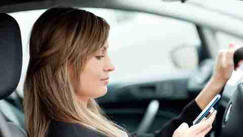 A woman texting while driving and showing signs of classic ADD with lack of focus, forgetfulness, and disorganization.
