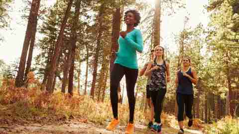 Women with ADHD running through the woods because exercise triggers dopamine creation in the ADD brain.