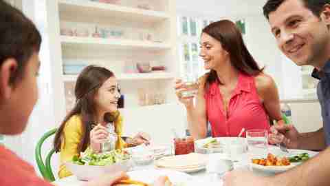 A family eating food prepared according to adhd friendly recipes together.