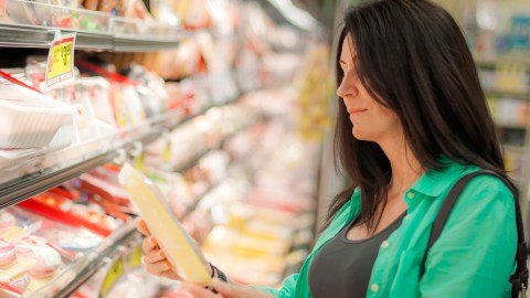 A woman picks out ADHD-friendly foods at the grocery store