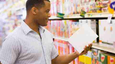 A man checks a nutrition label in the grocery store to make sure its ingredients don't make ADHD symptoms worse