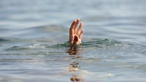 A person drowning with a hand above water, a metaphor for the emotional flooding that ADHD can cause.
