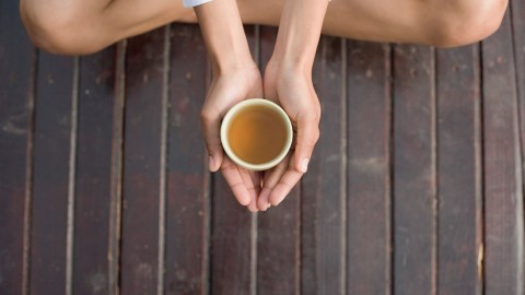 A woman holds a cup of tea. She's taking time for transitioning to the next task.